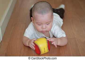 baby playing ball on floor