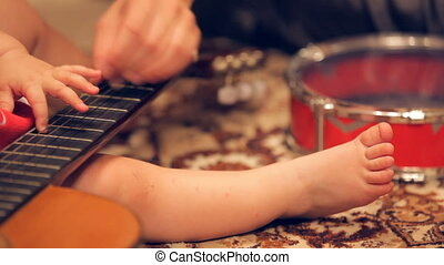 Baby playing guitar - Little child learning to play guitar