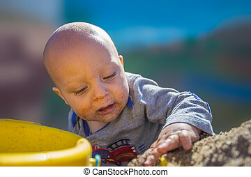 Baby playing in sand.