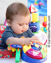 Baby playing - Cute baby with blue eyes playing in his...