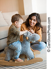 Baby playing with a rocking horse