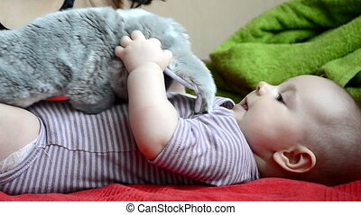 Baby playing with a toy rabbit