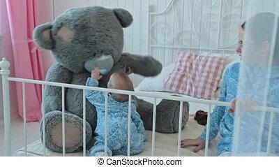 Baby playing with big teddy bear