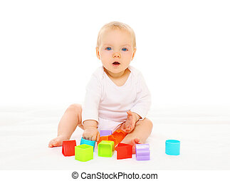 Baby playing with colorful toys on a white background