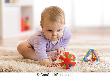 Baby playing with colorful toys sitting on a carpet at home