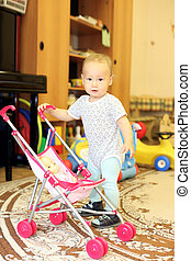 baby playing with doll and stroller