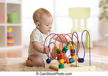 baby playing with educational toy in nursery - baby boy...