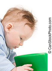 Baby playing with green plastic block