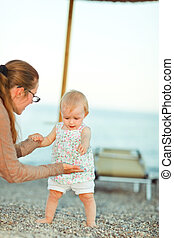 Baby playing with mother on beach