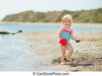 Baby playing with pail on sea shore