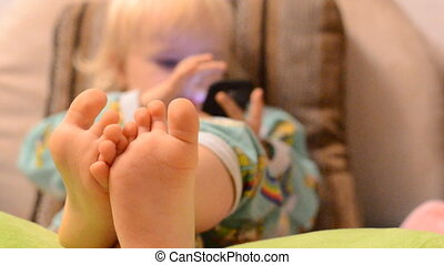 Baby playing with phone, focus on the legs