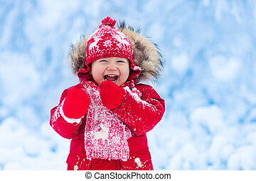 Baby playing with snow in winter. Little toddler boy in red...