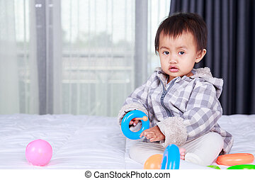 baby playing with toy on bed