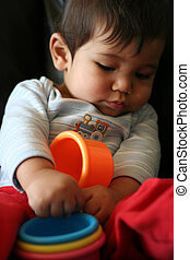 Baby playing with colorful toys while sitting on couch.