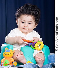 baby playing with toys - a cute 5 month old baby in bumbo...
