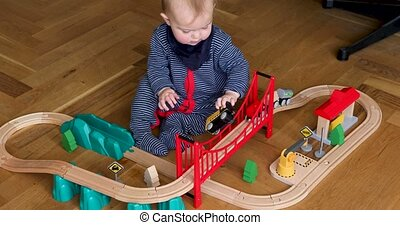 Baby playing with wooden railroad - From above little kid...