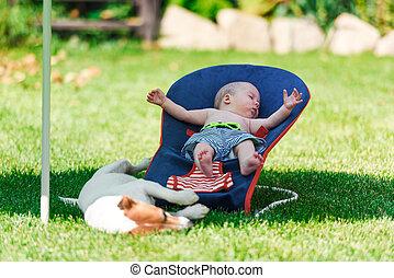 baby pojke, lögner, på, a, deck-chair, på, grön gräsmatta
