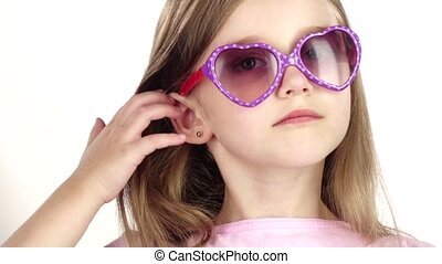 Baby posing for video cameras with glasses. White background. Close up. Slow motion
