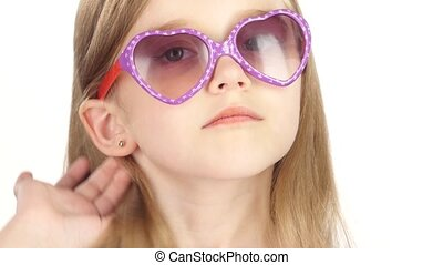 Baby posing for video cameras with glasses. White background. Close up