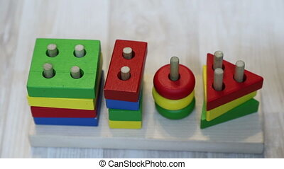 Baby puts a circle on the pin in a wooden constructor, slow ...