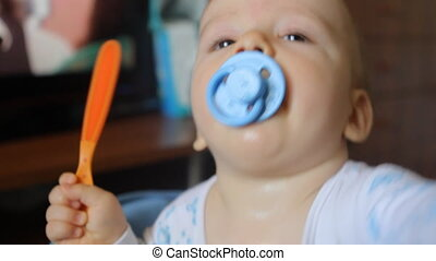 baby puts a pacifier in his mouth