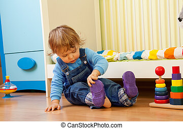 Baby learning putting on sandal sitting in the bedroom