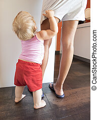 baby red shorts clutching mom leg in kitchen - blonde baby...