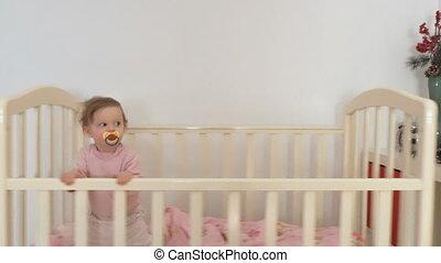 Baby rockingthe crib - Baby girl in the crib, swinging and...