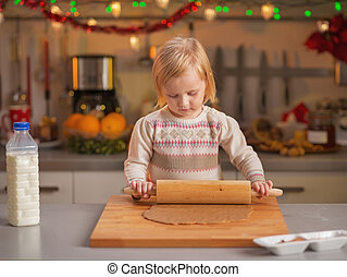 Baby rolling pin dough in christmas decorated kitchen