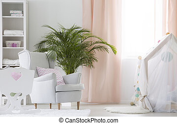 Baby room with armchair, crib and plant