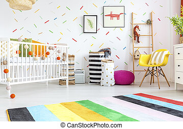Baby room with yellow chair and white cot