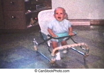 A cute little baby having a fun time running in his walker in the kitchen. (Scan from archival 8mm film)