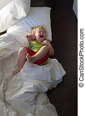 baby screaming on bed clothes floor