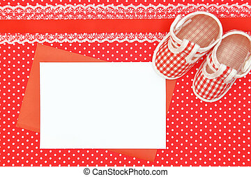 Baby shoes and blank card on polka dots background