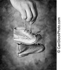 Baby Shoes - Black and white image of Man holding his old...