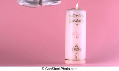 Baby shoes falling beside lit baptism candle on pink...