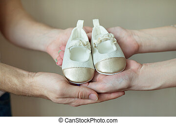 Baby shoes in the hands of parents
