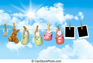 Baby shoes, pacifier and teddy bear on clothesline with blue...