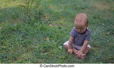 Baby siting on grass