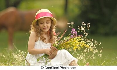 Baby sits in a clearing, turns over the torn wild flowers and makes a bouquet from them. Slow motion