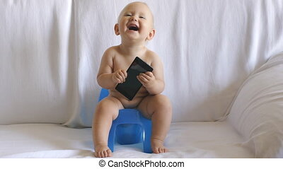 Baby sits on potty using smartphone