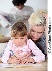 Baby-sitter and little girl doing homework