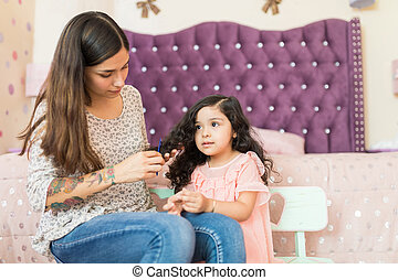 Baby Sitter Making Hair Of Girl In Bedroom