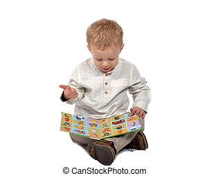 Baby sitting cross-legged reading a book - Baby dressed in a...
