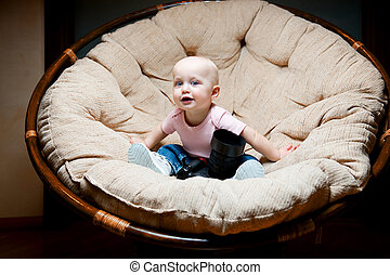 baby sitting in a chair with a large photo camera