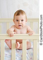 baby sitting in a crib