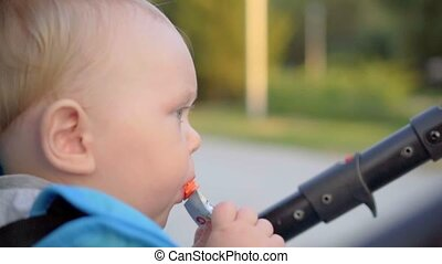 Baby sitting in a pram and eating a bag with baby food.