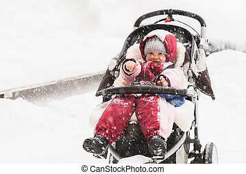 baby sitting in a stroller during snowfall