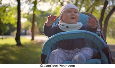 Baby sitting in a wheelchair, waving his hands and smiling.