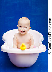 baby sitting in a white bath and smile